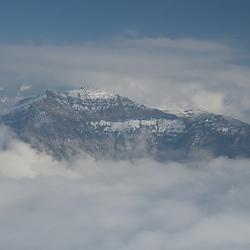 Aerial view through the clouds towards a spectacular mountain.