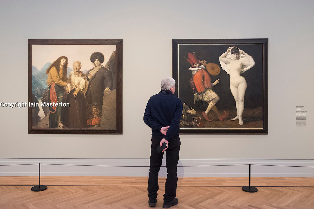 Visitor looking at GDR paintings, left, Three Women from Cefalu , right, The Jester and the Girl, by Werner Tuebke (Tübke),  at Museum Barberini in Potsdam Germany