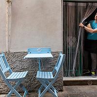 Italy, La Spezie Province, Young man peers from door of sidewalk cafe in Mediterranean coastal town of Porto Venere
