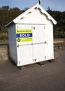 Banham Dark estate agent sold sign on white wooden beach hut at Felixstowe, Suffolk, England