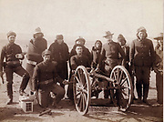 Corporal Paul Wienert and gunners of Battery 'E' 1st Artillery.   Seven Lakota native American Indian scouts and uniformed Euro-American soldiers pose with a Hotkiss field gun. Photograph c1891.