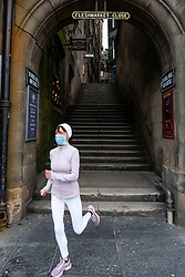 Female jogger wearing face mask running out of empty Fleshmarket Close during the coronavirus lockdown in Edinburgh Old Town, Scotland, UK