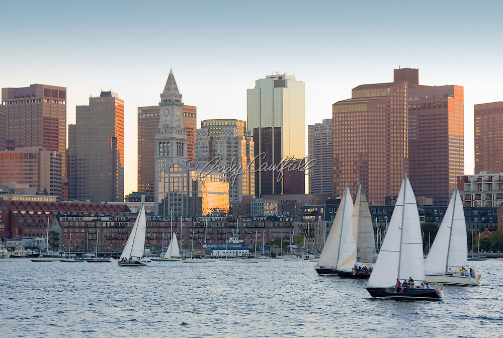 Sailboats in Boston Harbor pass the city's vibrant Waterfront and Financial district architecture, Boston, Massachusetts