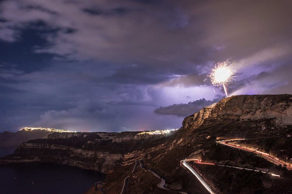 Fireworks explode on the cliffside of the island of Santorini in Greece, as lightning fills the sky with glowing clouds at night