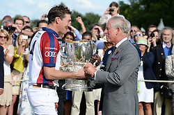 Left to right, Audi England captain LUKE TOMLINSON receives the Westchester Cup from HRH The PRINCE OF WALES at the Audi International Polo at Guards Polo Windsor Great Park, Egham, Surrey on 28th July 2013.