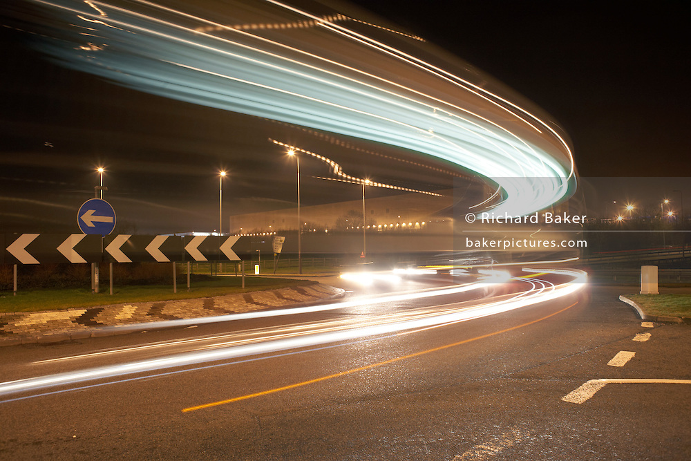 Lights from industrial night traffic speeding on the A5 at the DIRFT warehouse logistics park in Daventry,