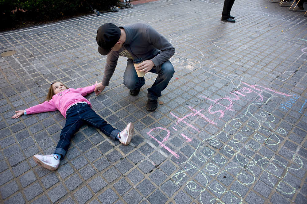 Jason DiNitto, of New Kensington, traces an outline of his daughter Elena DiNitto, age 5, onto Katz Plaza during the Pittsburgh Cultural Trust Fall Gallery Crawl in downtown Pittsburgh.