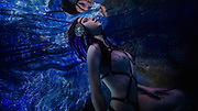 Brunette Woman with Blue Feathered Headdress floats underwater<br /> <br /> Underwater Beauty by Craig Minielly