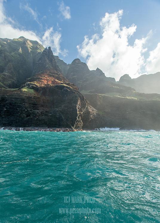The dramatic Napali Coast rises steeply above the surk on Kauai's northwest corner.