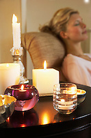 Woman Relaxing on sofa beside table with Candles
