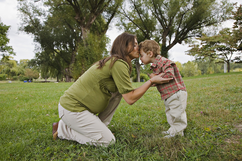 Pregnant mom kissing toddler in park