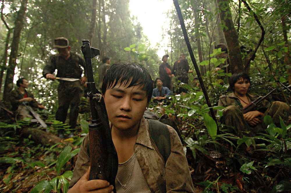 A young boy stands guard in the jungle while his group rests, near Vang Vieng, Laos, June 30, 2006...Pictured are a group of Hmong people who report an attack against them April 6, 2006 by Lao and Vietnamese military forces.  26 people perished, 5 were injured, and 5 babies died shortly after because their dead mothers could not breast-feed them.  Only one adult male was killed, the other 25 victims were women and children (17 children).  The Lao Spokesman for the Ministry of Foreign Affairs says this is a fabrication, an investigation has been completed, and there was no attack.  The Hmong group says no officials have interviewed witnesses or visited the crime scene, a point the Lao Spokesman did not deny.  ..The Hmong people pictured have hidden in remote mountains of Laos for more than 30 years, afraid to come out.  At least 1,000 are said to exist, with little food, scavenging in the jungle. Most have not seen the modern world.  The CIA trained and funded many Hmong hill tribes in Laos from 1961 to 1973 to fight communism.  The Hmong suffered massive casualties defending their homeland.  When America withdrew from the conflict most Hmong were left alone to face the might of the North Vietnamese Army.  The Royal Lao Government fell to the communists and the Hmong became outcasts in the country they fought to defend.  Since 1975, under the communists, thousands of reports evidence the Hmong have suffered frequent persecution, torture, executions, imprisonment, and possible chemical weapons attacks.  Reports of these atrocities continue to this day.  The Lao Government generally denies the jungle people exist or that any of this is happening.  The Hmong group leader, Blia Shoua Her, says they are not part of the Hmong resistance and want peace.  He claims they are just civilians defending their families, hoping to surrender to the UN.......
