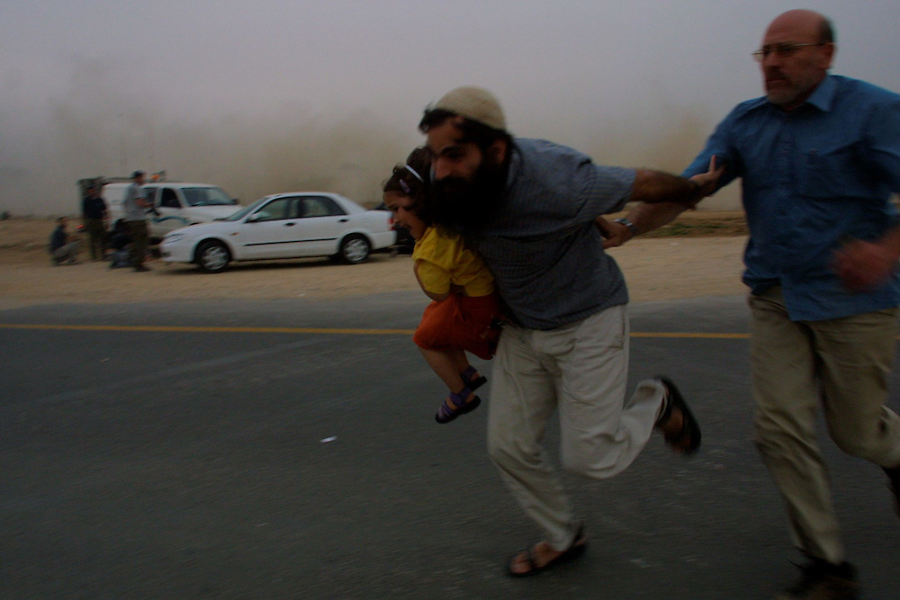 Jewish settlers and relatives of Tali Hatuel, take cover as Palestinian gunmen open fire against them during a memorial ceremony. The ceremony for Tali Hatuel, who was killed with her four daughters, Hila, 11, Hadar, 9, Roni, 7, and Merav, 2, on May 2 by Palestinian gunmen on the Kissufim main road leading to the Gush Katif settlement block in the southern Gaza Strip. No casualties were reported. Hatuel was pregnant with her fifth child when she was killed.