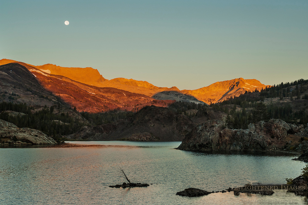 Full moon setting over mountains at sunrise over Ellery Lake, near Tioga Pass, Eastern Sierra, California