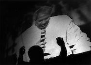 Fundamentalist Christian Pilgrim raises hands to a gigantic monitor projecting image of Benny Hinn, Benny Hinn Miracle Crusade, Manila, Philippines.