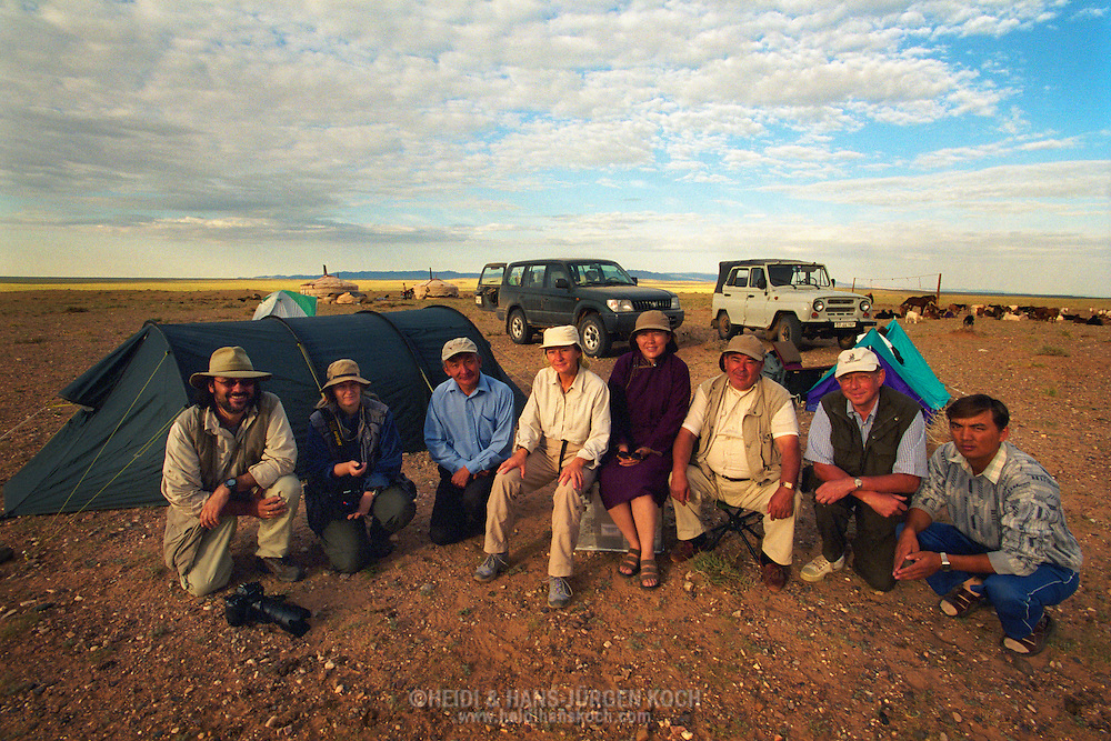 Mongolei, MNG, 2003: Kamel (Camelus bactrianus). Aufnahme des kompletten Expeditionsteams (von links nach rechts): Hans-Juergen Koch - Fotograf, Heidi Koch - Fotograf, Dr. Erdenebilek - Tierarzt, Dr. Hania Luczak - Redakteurin, Geo Deutschland,  Dr. Otgon - Tierarzt ,  Dr. Werner Theinert - Tierarzt, Prof. Dr. Horst Geilhausen - Tierarzt, Baterdene - Fahrer, vor ihrem Camp, Süd-Gobi.   Mongolia, MNG, 2003: Workshop, complete expedition team from left to right: Hans-Juergen Koch - Photographer, Heidi Koch - Photographer, Dr. Erdenebilek - Veterinarian of the South Gobi, Dr. Hania Luczak - editor from Geo Germany,  Dr. Otgon - Veterinarian ,  Dr. Werner Theinert - Veterinarian, Prof. Dr. Horst Geilhausen - Veterinarian, Baterdene - Driver, in front of their camp, South Gobi.  