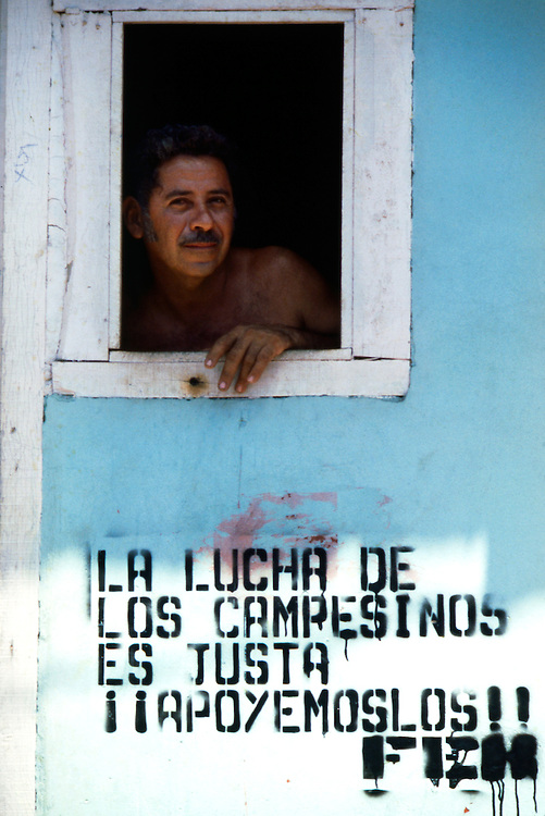 """A resident of Masaya, Nicaragua looks from his window below which is the political slogan """"The struggle of the peasants is just. Let's support them!"""" during the Civil War in Nicaragua - 1978"""