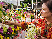 "22 JULY 2013 - PHRA PHUTTHABAT, THAILAND:  A woman places flowers on the truck carrying the Buddha during the Tak Bat Dok Mai at Wat Phra Phutthabat in Saraburi province of Thailand, Monday, July 22. Wat Phra Phutthabat is famous for the way it marks the beginning of Vassa, the three-month annual retreat observed by Theravada monks and nuns. The temple is highly revered in Thailand because it houses a footstep of the Buddha. On the first day of Vassa (or Buddhist Lent) people come to the temple to ""make merit"" and present the monks there with dancing lady ginger flowers, which only bloom in the weeks leading up Vassa. They also present monks with candles and wash their feet. During Vassa, monks and nuns remain inside monasteries and temple grounds, devoting their time to intensive meditation and study. Laypeople support the monastic sangha by bringing food, candles and other offerings to temples. Laypeople also often observe Vassa by giving up something, such as smoking or eating meat. For this reason, westerners sometimes call Vassa the ""Buddhist Lent.""    PHOTO BY JACK KURTZ"