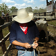 "A man counts out his debt from a friendly bet as other cowboys compete in a lasso competition in San Carlos, near Boquete, Panama, on February 11, 2007. In the competition, each heat features one town's team versus another in a tournament bracket style. The speed of the calf's capture determines points. ..""Bet Debt"""
