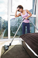 Tired African American woman vacuuming in bedroom