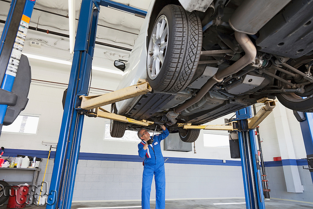 Low angle view of mechanic working under car