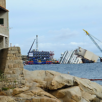 ISOLA DEL GIGLIO, ITALY - SEPTEMBER 15:  The wreckage of the Costa Concordia is seen from the end of the pier on September 13, 2013 in Isola del Giglio, Italy. The Costa Concordia is reportedly due to be righted beginning on the morning of September 16, then, if the operation is successful, it will be towed away and scrapped.  (Photo by Marco Secchi/Getty Images)