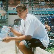 Teenage boy sitting on a concrete fence eating a bag of crisps, Brazil
