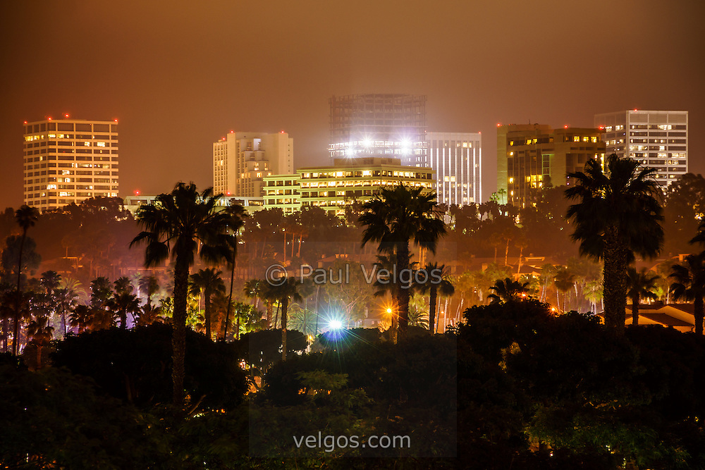 Photo of Newport Beach skyline at night with Newport Beach office buildings and palm trees.