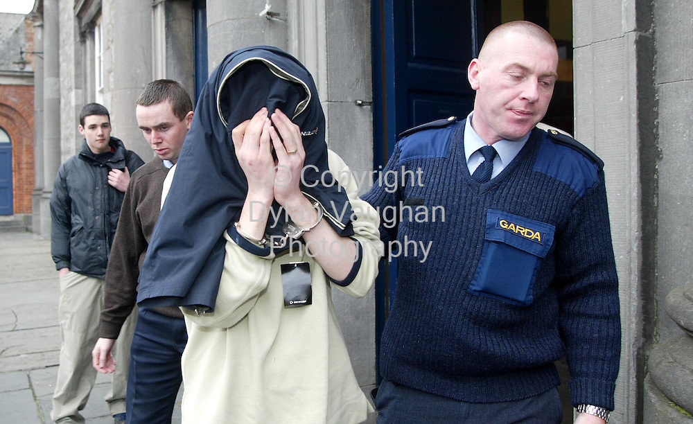 12/3/2002 Irish Independent News.Charles Maher (covered) being led from Kilkenny Court yesterday in connection with the stabbing of John Paul Ryan in Waterford..Picture Dylan Vaughan