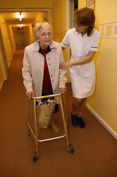 Carer helping an elderly woman along with her walking frame in sheltered accommodation,