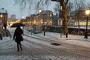 Een vrouw loopt aan de begin van de avond door de sneeuw in Utrecht