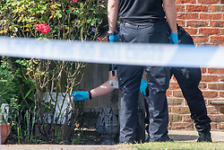 © Licensed to London News Pictures. 21/05/2020. Beaconsfield, UK. ***NOTE TO EDITORS ID BADGE PIXELATED*** Specialist search team members look for evidence at a property on North Drive. Thames Valley Police were called to North Drive, Beaconsfield at around 00:01 BST on Thursday 21/05/2020 to a report of a stabbing. A man in his forties had sustained injuries consistent with stab wounds and was taken to hospital. Photo credit: Peter Manning/LNP