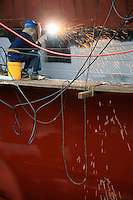Welder working on side of ship in dry dock