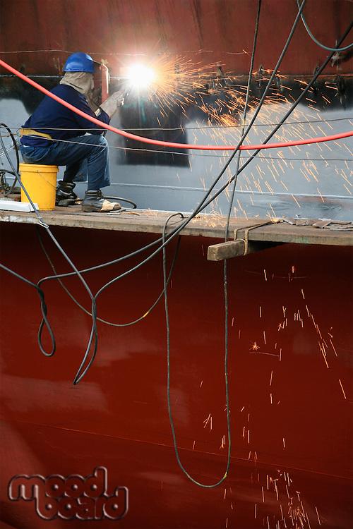Welder working on side of ship in dry dock