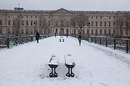 France. Paris. Art bridge on the  Seine river  under the snow, Louvre museum in the distance/ Paris sous la neige en hiver. le pont des Arts sur la Seine,