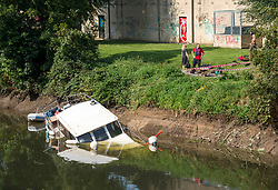 """© Licensed to London News Pictures; 16/09/2020; Bath, UK. The canal boat """"Pollyanna"""" is seen partly submerged on the river Avon in Bath. Canal boats were evacuated and some boats sunk on the river Avon at Twerton after the sluice gates failed yesterday evening (15 September) and the water level dropped dramatically. The Fire Service assisted. The Canal and River Trust have issued a statement saying a drop in water level on the River Avon was caused by a failure of the Environment Agency's sluice gates and that the sudden and dramatic drop in levels meant that it was impossible to give warning to the boaters. The Canal and River Trust say they understand the difficulties faced by the EA in repairing the sluice and this is the second time this has happened, so they are looking to the EA to find a solution as a matter of urgency.  Photo credit: Simon Chapman/LNP."""