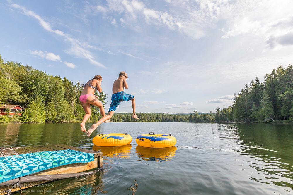 Kids jump into Island Pond at Red River Camps in Aroostook County, Maine. Deboullie Public Reserve Land.