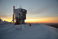 The sun sets behind the Mount Washington Observatory tower, Mt. Washington, New Hampshire.