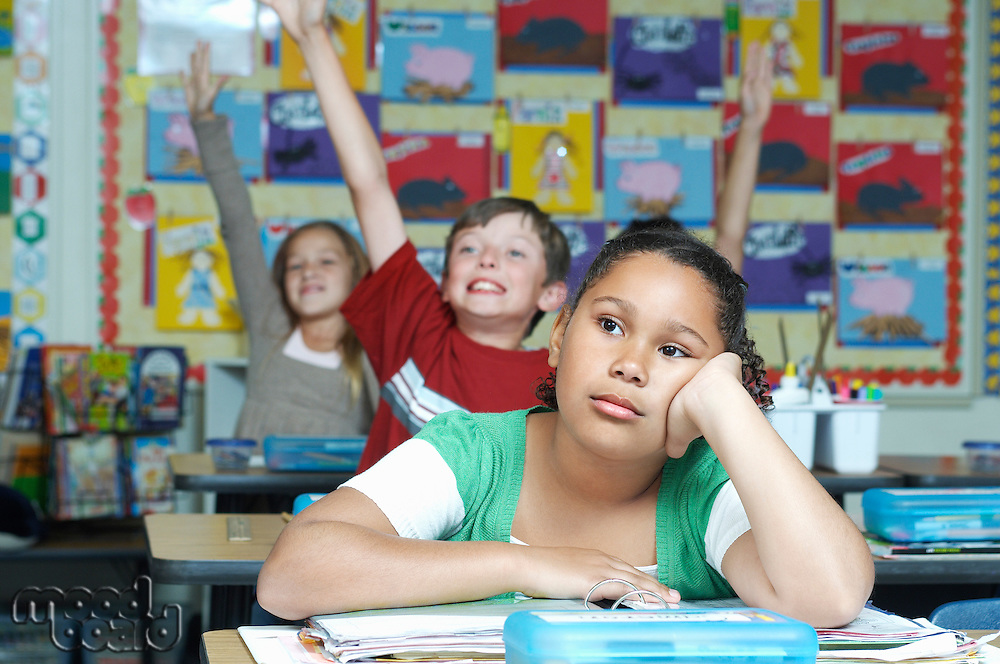 Three pupils in classroom, two with raised hands, one pensive