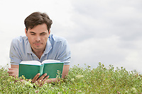 Young man reading book while lying on grass against sky