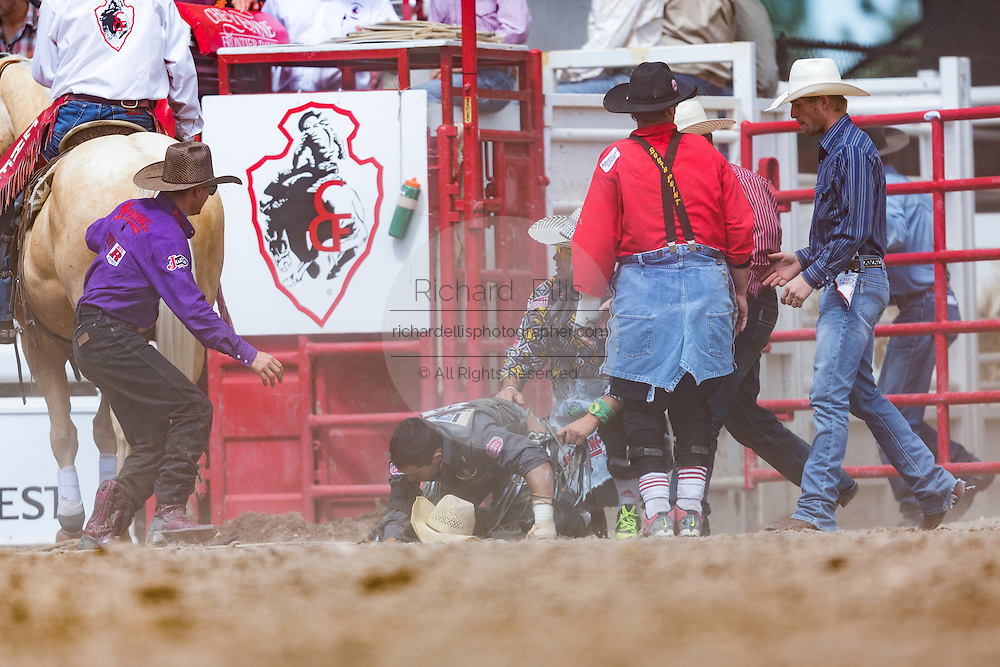 Officials and a doctor rush to check Bull rider Lon Danley after he was gored by a bull during the Bull Riding finals at the Cheyenne Frontier Days rodeo in Frontier Park Arena July 26, 2015 in Cheyenne, Wyoming. Danley was uninjured and walked off the arena.