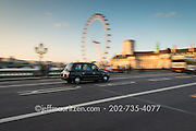 A black London cab drives over Westminster Bridge in South Bank in London, England.