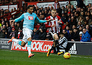 Derby County Defender Cyrus Christie gets a tackle in to stop a Brentford break down the wing during the Sky Bet Championship match between Brentford and Derby County at Griffin Park, London, England on 20 February 2016. Photo by Andy Walter.