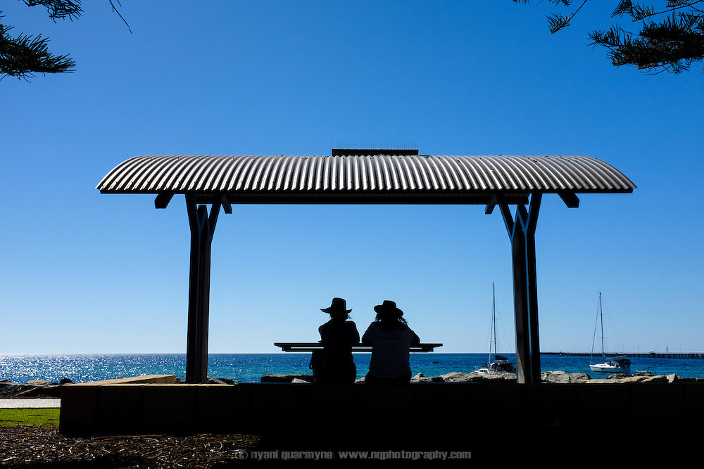 People seated at a beachside picnic table in Busselton, Western Australia.