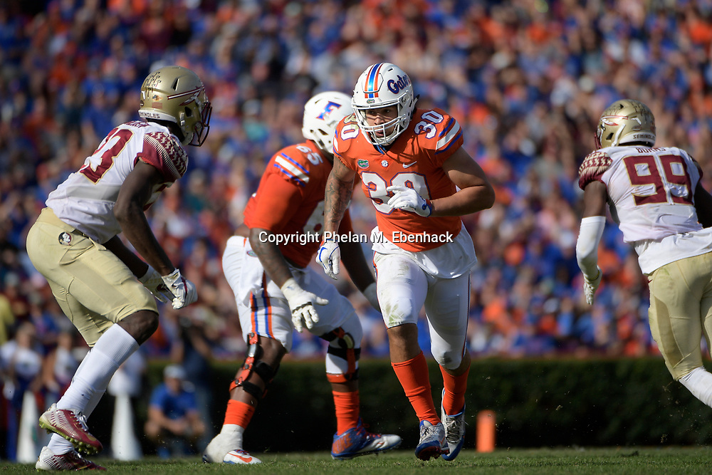 Florida tight end DeAndre Goolsby (30) runs a route in front of Florida State defensive back Hamsah Nasirildeen (23) during the second half of an NCAA college football game Saturday, Nov. 25, 2017, in Gainesville, Fla. FSU won 38-22. (Photo by Phelan M. Ebenhack)