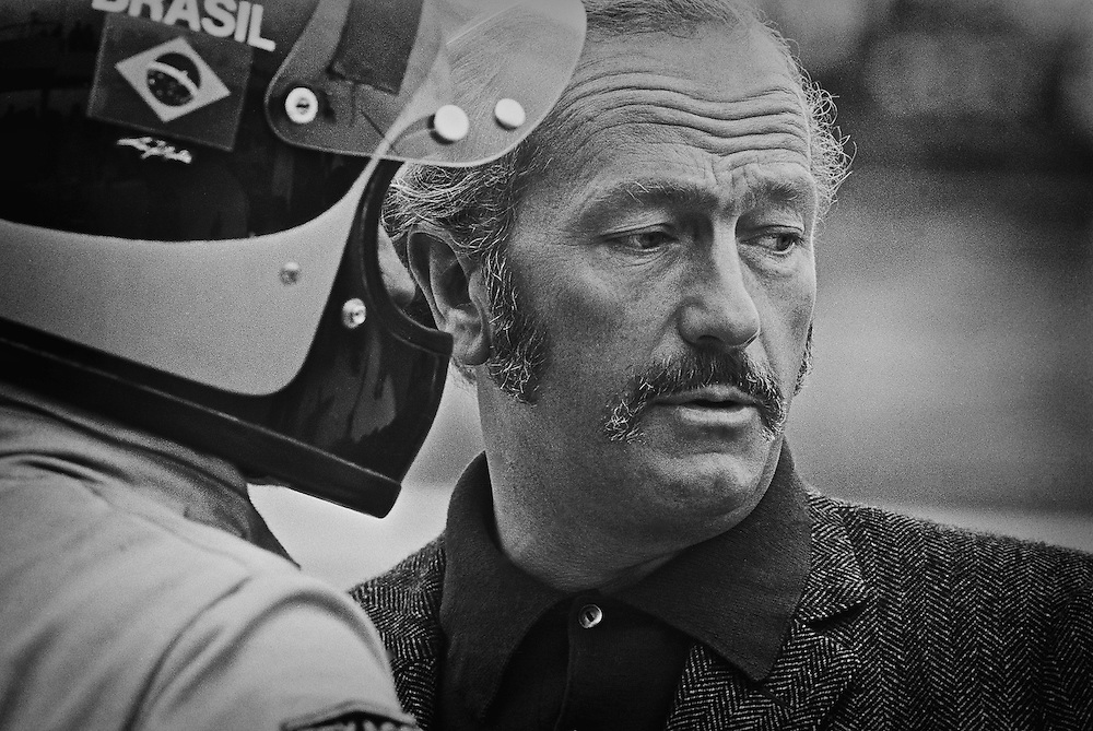 Colin Chapman, founder of Lotus and team principle of Team Lotus F1, discusses practice testing for the 1972 United States Grand Prix with newly-crowned Formula One Drivers' Champion, Emerson Fittipaldi. <br />