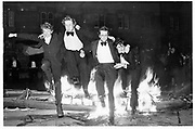 Jumping over the burning boat. Eights Week, Oxford, Oriel. (left to right) Paul Sharpe, Rev. Paul Burholt, Nick Rowland, Will Treasure. 1981© Copyright Photograph by Dafydd Jones 66 Stockwell Park Rd. London SW9 0DA Tel 020 7733 0108 www.dafjones.com