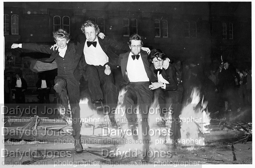 Jumping over the burning boat. Eights Week, Oxford, Oriel. (left to right) Paul Sharpe, Rev. Paul Burholt, Nick Rowland, Will Treasure. 1981© Copyright Photograph by Dafydd Jones 66 Stockwell Park Rd. London SW9 0DA Tel 020 7733 0108 www.dafjones.com