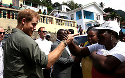 Prince Harry meets well wisher Avis Collis during a visit to the hillside village of Vermont on the island of Saint Vincent, St Vincent and the Grenadines, during the second leg of his Caribbean tour.