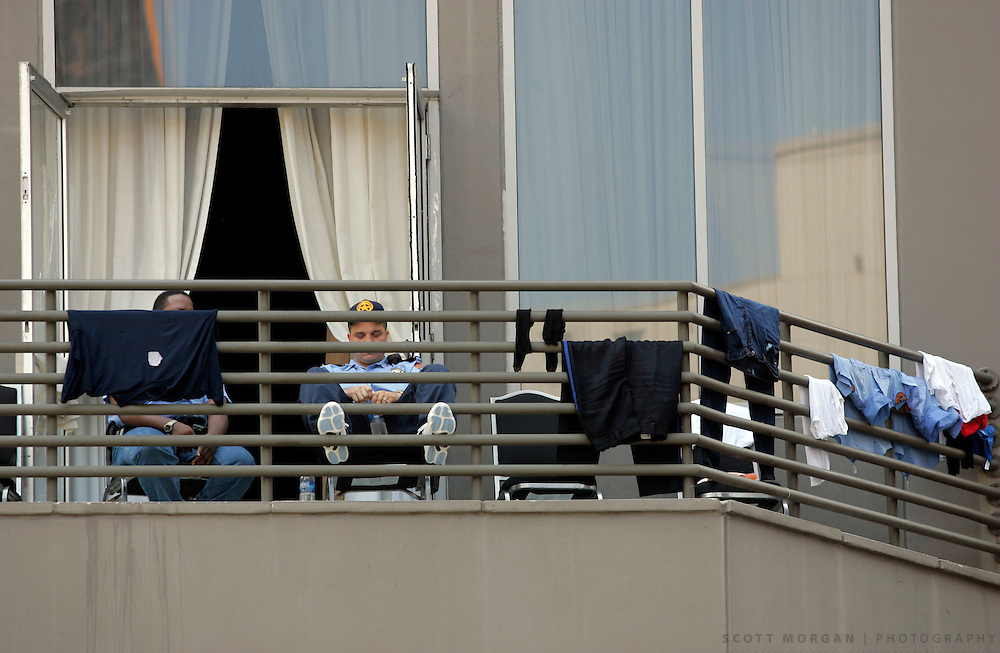 Police officers rest and dry their clothes from a balcony on Canal Street Wednesday, August 31, 2005, in New Orleans, La. Officers were getting dry shoes and socks from downtown shoe stores. Scott Morgan